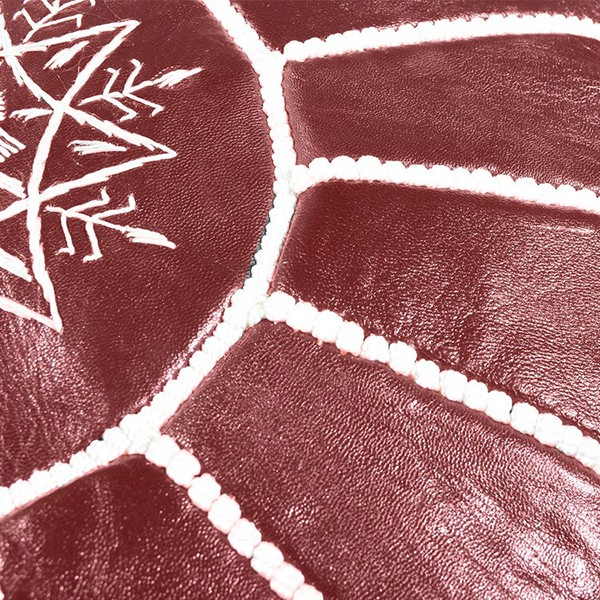 Dark red leather pouf with white arabesques