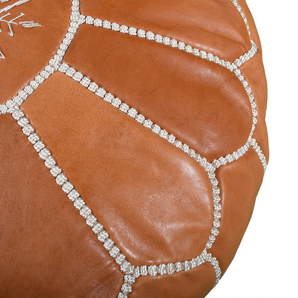 Light brown leather pouf with white arabesques